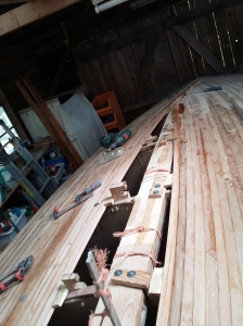Planks curving as a result of the varying length from keel to deck.